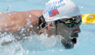 Michael Phelps warms up prior to competing in the 100-meter butterfly during the Arena Grand Prix, Thursday, April 24, 2014, in Mesa, Ariz. It is Phelps' first competitive event after a nearly two-year retirement. (AP Photo/Matt York)