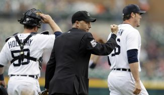Home plate umpire Dan Iassogna signals the out call on Chicago White Sox's Marcus Semien on at attempted steal of second base because of batter interference, during the ninth inning of a baseball game in Detroit, Thursday, April 24, 2014. The Tigers won 7-4.  (AP Photo/Carlos Osorio)