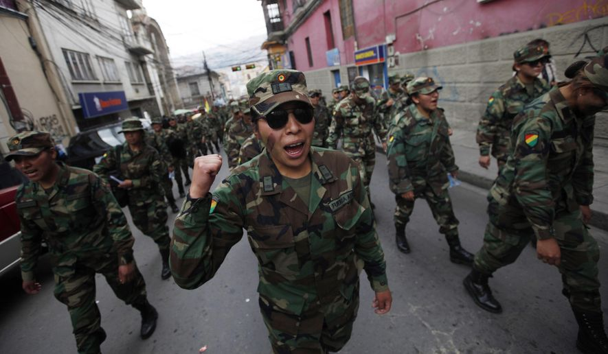 A female Air Force Sergeant joins the third day of protests by low ranking soldiers in La Paz, Bolivia, Thursday, April 24, 2014. The soldiers marched for a third day against the military high command's dismissal of four of its leaders who defended their call for better career opportunities. Enlisted men and women are demanding changes so that non-commissioned officers in Bolivia's military may study to become career officers. (AP Photo/Juan Karita)