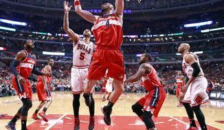 Washington Wizards center Marcin Gortat (4) grabs a rebound over Chicago Bulls forward Carlos Boozer (5) during the first half of Game 2 in an opening-round NBA basketball playoff series game Tuesday, April 22, 2014, in Chicago. Also watches on the play are John Wall (2), Trevor Booker (35) and Taj Gibson (22). (AP Photo/Charles Rex Arbogast)