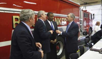 U.S. Transportation Secretary Anthony Foxx, second from right, is flanked by North Dakota Gov. Jack Dalrymple, North Dakota Rep. Kevin Cramer, left, and North Dakota Sen. John Hoeven, right, during a meeting on rail safety in Casselton, N.D., Thursday, April 24, 2014. (AP Photo/Dave Kolpack)