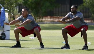Arizona Cardinals' Michael Floyd, left, and Antonio Cromartie stretch during the first phase of the voluntary offseason training program at the NFL football team's training facility on Thursday, April 24, 2014, in Tempe, Ariz. (AP Photo/Ross D. Franklin)