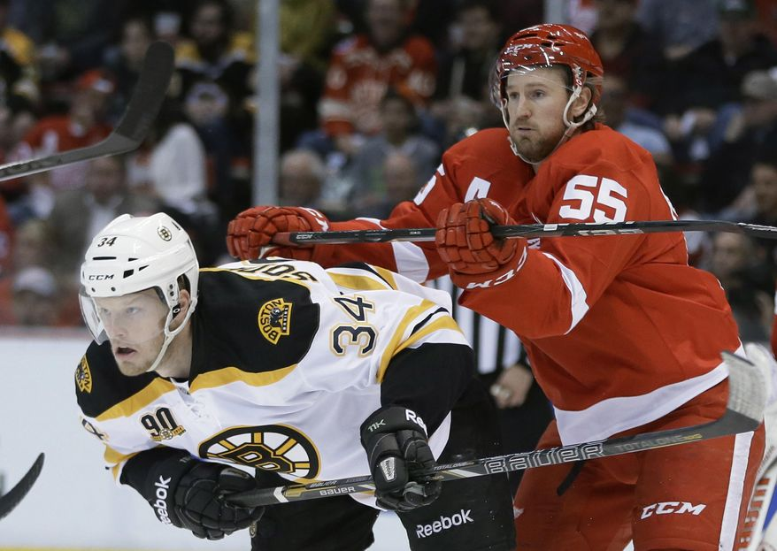 Detroit Red Wings defenseman Niklas Kronwall (55)checks Boston Bruins center Carl Soderberg (34) during the first period of Game 4 of a first-round NHL hockey playoff series in Detroit, Thursday, April 24, 2014. (AP Photo/Carlos Osorio)