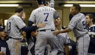 San Diego Padres' Chase Headley is congratulated in the dugout after hitting a home run during the 12th inning of a baseball game against the Milwaukee Brewers Tuesday, April 22, 2014, in Milwaukee. (AP Photo/Morry Gash)