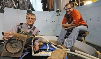 Peter Sorensen, left, a University of Minnesota professor of fisheries and aquatic biology, and doctoral student Dan Zielinski, right, sit in a 10,000- liter experiment tank on Wednesday, April 23, 2014, in their lab in St. Paul, Minn. in which they have created sound and bubble barriers to divert invasive Asian Carp. Sorensen, the director of the Aquatic Invasive Species Research Center, holds an underwater speaker. They hope to receive $60,000 in funding to order and install five 196-decibel speakers at the Lock & Dam #8 on the Mississippi River at Genoa, Wis. to stop the spread of bighead and silver carp, which are successfully breeding below the dam.  (AP Photo/ Pioneer Press, Scott Takushi)