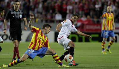 Sevilla's Nico Pareja, right, and Valencia's Fede Cartabia from Argentina, left, vie for the ball during their Europa League semifinal first leg soccer match at the Ramon Sanchez Pizjuan stadium, in Seville, Spain on Thursday, April 24, 2014. (AP Photo/Miguel Angel Morenatti)