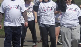 "In this April 5, 2014 photo, former Quincy University student Shannon Peters, center, pumps her fist she heads out on a one-mile walk around the school's campus with her mother and father, Matt, left, and Mary Peters. The walk was part of the ""Strides for Shannon"" fundraiser. Shannon Peters was seriously injured when struck by a car on Jan. 7, 2013. (AP Photo/The Quincy Herald-Whig, Phil Carlson)"