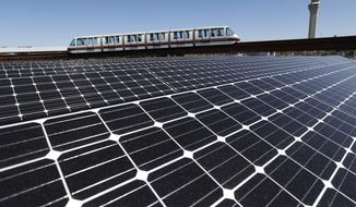 Solar panels that were recently placed on the roof of the building supplying energy to the AirTrain at Newark Liberty International Airport are seen as the train rolls by, Thursday, April 24, 2014, in Newark, N.J. According to The Port Authority of New York & New Jersey, the 3,200-solar panel installation spread among four building rooftops will supply the airport with 0.7 MW, equivalent to powering 61 homes with electricity, conserving 992 barrels of oil or removing 90 passenger vehicles from the road each year. (AP Photo/Julio Cortez)
