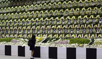 A girl pays tribute to the victims of the sunken ferry Sewol during a temporary memorial at the auditorium of the Olympic Memorial Museum in Ansan, south of Seoul, South Korea, Thursday, April 24, 2014. Angry relatives of some of the more than 130 people still missing from the sinking of the ferry Sewol surrounded the fisheries minister and the coast guard chief Thursday, preventing them from leaving the area where families have been waiting for word of their loved ones for more than a week. (AP Photo/Lee Jin-man)