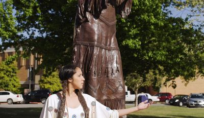 This photo provided by the University of Science and Arts shows actress Tana Takes Horse posing in front of a statue of Chickasaw storyteller Te Ata Thompson Fisher at the University of Science and Art in Chickasha, Okla. on Friday, April 25, 2014. Political leaders, Native American tribal members, scholars and community members gathered Friday to dedicate athestatue of the renowned storyteller who broke stereotypes over her six-decade career. (AP Photo/University of Science and Arts, Taylor G. Preston)
