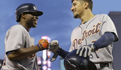 Detroit Tigers' Nick Castellanos, right, celebrates with Torii Hunter, left, after Castellanos scored on single by Rajai Davis off Minnesota Twins pitcher Anthony Swarzak during the third inning of a baseball game in Minneapolis, Friday, April 25, 2014.  (AP Photo/Ann Heisenfelt)