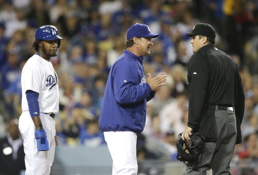 Los Angeles Dodgers manager Don Mattingly, center, argues with home plate umpire Mike DiMuro after Hanley Ramirez, left, was called out at home plate during the fifth inning of a baseball game against the Philadelphia Phillies on Thursday, April 24, 2014, in Los Angeles. (AP Photo/Jae C. Hong)