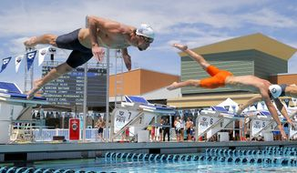 Michael Phelps leaps at the start of a 50-meter freestyle preliminary heat during the Arena Grand Prix swim event, Friday, April 25, 2014, in Mesa, Ariz. It is Phelps' second competitive event after a nearly two-year retirement. (AP Photo/Matt York)