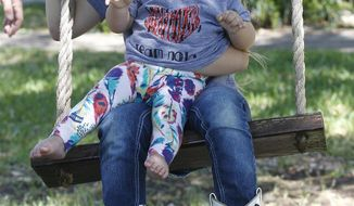 Nola Carter, 15 months, swings with her sister Caden, 6, in the front yard of their Friendswood home on Tuesday afternoon April 15, 2014. Nola was diagnosed with Sanfilippo syndrome A around her first birthday. (AP Photo/The Galveston County Daily News, Kevin M. Cox)