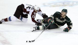 Minnesota Wild center Mikko Koivu (9), of Finland, and Colorado Avalanche right wing P.A. Parenteau (15) fall as they chase the puck during the third period of Game 4 of an NHL hockey first-round playoff series in St. Paul, Minn., Thursday, April 24, 2014. The Wild won 2-1. (AP Photo/Ann Heisenfelt)