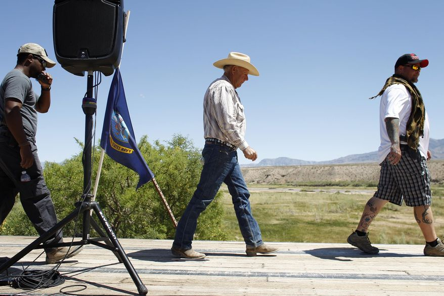 Rancher Cliven Bundy, center, walks on stage to speak at a press conference near Bunkerville, Nev., Thursday, April 24, 2014. Bundy, a Nevada rancher who became a conservative folk hero for standing up to the government in a fight over grazing rights, lost some of his staunch defenders Thursday after wondering aloud whether blacks might have had it better under slavery. (AP Photo/Las Vegas Review-Journal, John Locher)