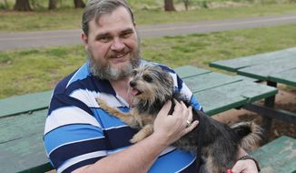 Jerry Starr is pictured with Tobi, his four-year-old shih tzu-yorkie mix dog at a park in Del City, Okla., Thursday, April 17, 2014. Starr was not allowed to take the dog into a shelter during the May 20, 2013 tornado and opted to stay outside the shelter in his car with his dog. (AP Photo/Sue Ogrocki)