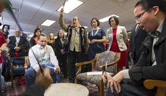 Clyde Bellecourt, also known as Thunder Before the Storm, holds up a condor feather after leading a prayer as the Ringing Shield Drum circle sings before the Minneapolis City Council unanimously voted  on Friday, April 25, 2014, in Minneapolis, to rename Columbus Day, Indigenous People's Day (AP Photo/The Star Tribune, Courtney Perry)  MANDATORY CREDIT; ST. PAUL PIONEER PRESS OUT; MAGS OUT; TWIN CITIES TV OUT