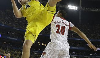 "FILE - In this April 8, 2013 file photo, Michigan forward Mitch McGary (4) comes down with the rebound as Louisville guard/forward Wayne Blackshear (20) looks on during the first half of the NCAA Final Four tournament college basketball championship game in Atlanta. McGary is entering the NBA draft, saying he had little choice after testing positive for marijuana during the NCAA tournament. ""I am ready to move on to the next stage in my life and enter the NBA draft,"" the 6-foot-10 McGary said in a statement released by the school Friday, April 25, 2014. (AP Photo/David J. Phillip, File)"