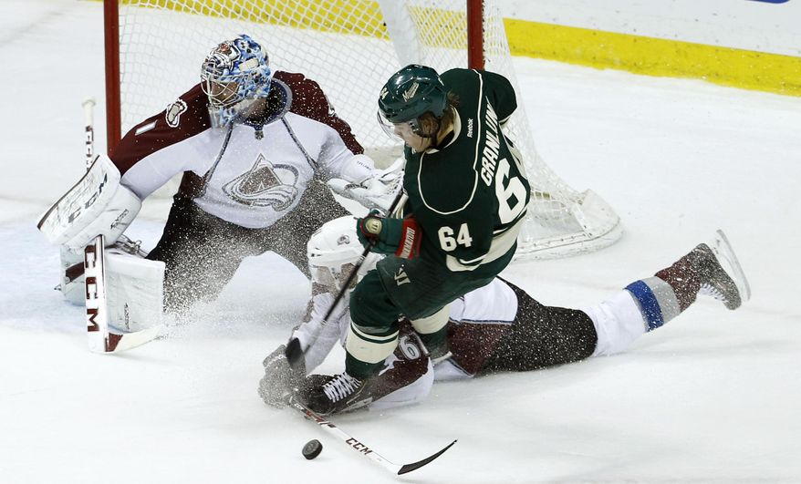 Colorado Avalanche defenseman Andre Benoit and Minnesota Wild center Mikael Granlund (64), of Finland, battle for the puck in front of Avalanche goalie Semyon Varlamov (1), of Russia, during the first period of Game 4 of an NHL hockey first-round playoff series in St. Paul, Minn., Thursday, April 24, 2014. (AP Photo/Ann Heisenfelt)