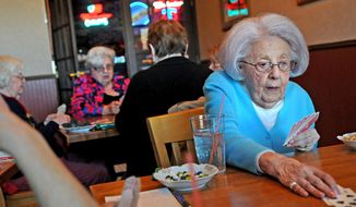 """ADVANCE FOR RELEASE SATURDAY, APRIL 26, 2014, AND THEREAFTER - In this April 10, 2014 photo, Betty Sweet, right, lays down a card during a bridge game at Champps restaurant in St. Paul, Minn. The """"girls,"""" as the players call themselves, are in their 80s and 90s, and have gathered monthly for nearly 60 years to play bridge and chat. (AP Photo/The St. Paul Pioneer Press, Jean Pieri)  MINNEAPOLIS STAR TRIBUNE OUT"""