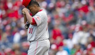 Cincinnati Reds relief pitcher Alfredo Simon (31) adjust his cap after hitting Washington Nationals' Ryan Zimmerman with a pitch during the 10th inning of a baseball game Thursday, April 12, 2012, in Washington. Zimmerman scored on a wild pitch for a 3-2 Nationals victory. (AP Photo/Evan Vucci)
