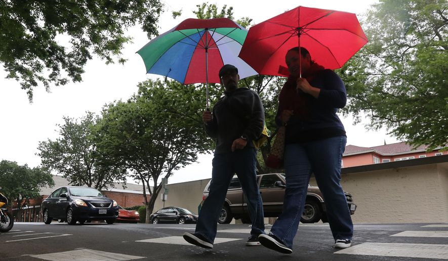 Raffa Chavez, left, and Gloria Sandoval use umbrellas during a late-season storm in Sacramento, Calif. on Friday, April 25, 2014. While bringing much needed rain and snow to California it is not expected to make much of a dent in the state's drought. (AP Photo/Rich Pedroncelli) ** FILE **