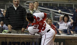 Washington Nationals catcher Jose Lobaton runs into the wall as he tries to catch a could ball by San Diego Padres' Tommy Medica during the 12th inning of a baseball game at Nationals Park on Thursday, April 24, 2014, in Washington. The Padres won 4-3 in 12 innings. (AP Photo/Alex Brandon)