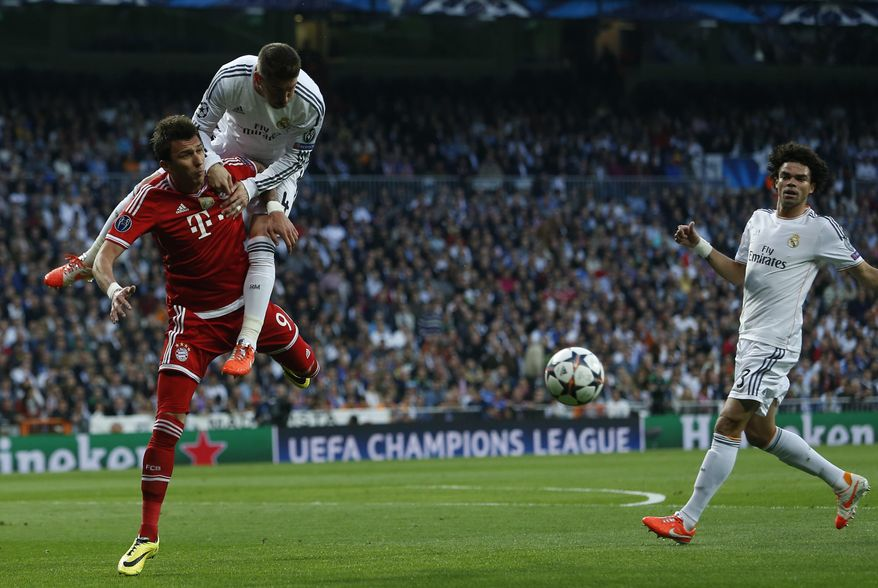 Bayern's Mario Mandzukic jumps for the ball with Real's Sergio Ramos and Pepe, right, during a first leg semifinal Champions League soccer match between Real Madrid and Bayern Munich at the Santiago Bernabeu stadium in Madrid, Spain, Wednesday, April 23, 2014. (AP Photo/Andres Kudacki)