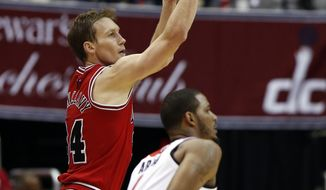 Chicago Bulls forward Mike Dunleavy (34) shoots over Washington Wizards forward Trevor Ariza during the second half of Game 3 of an opening-round NBA basketball playoff series, Friday, April 25, 2014, in Washington. Dunleavy had 35 points as the Bulls won 100-97. (AP Photo/Alex Brandon)