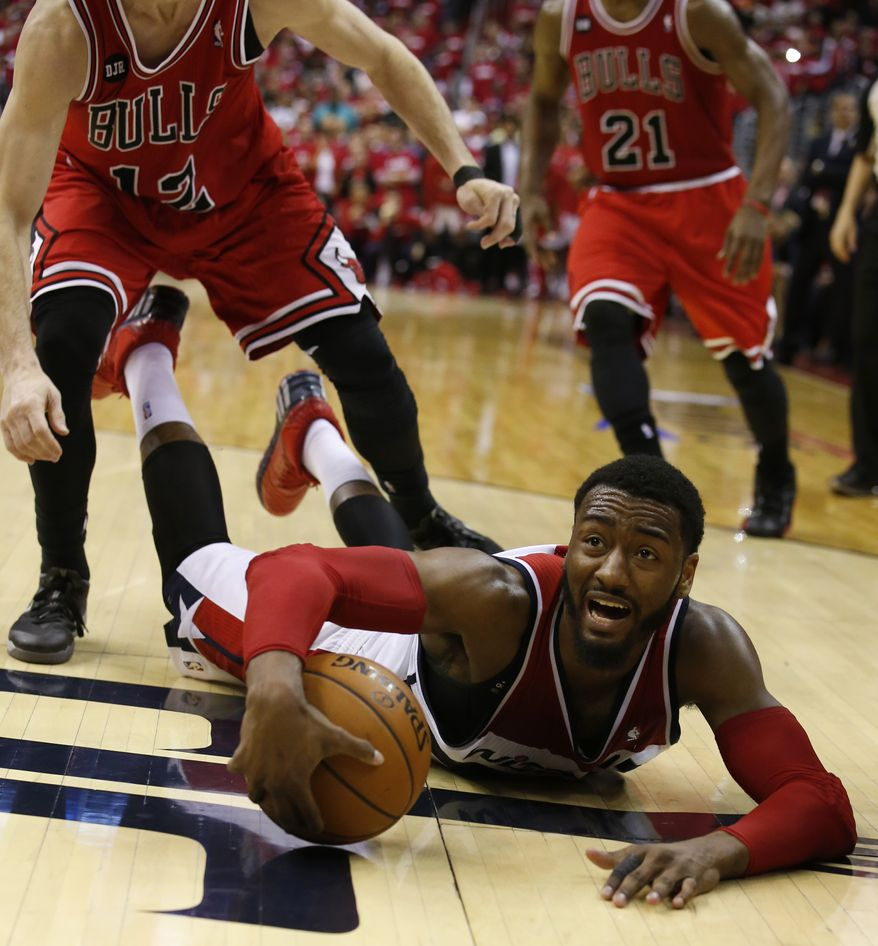 Washington Wizards guard John Wall calls a timeout as he falls to the court with the ball in the second half of Game 3 of an opening-round NBA basketball playoff series against the Chicago Bulls, Friday, April 25, 2014, in Washington. The Bulls won 100-97. (AP Photo/Alex Brandon)