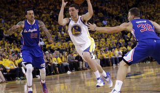Golden State Warriors' Klay Thompson (11) dribbles between Los Angeles Clippers' Matt Barnes (22) and Blake Griffin (32) during the second half in Game 3 of an opening-round NBA basketball playoff series on Thursday, April 24, 2014, in Oakland, Calif. Los Angeles won 98-96. (AP Photo/Marcio Jose Sanchez)