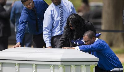 Sharon Blair, second from right, mother of U.S. Navy Petty Officer 2nd Class Mark Mayo, of Hagerstown, Md., puts her hand on her son's casket during his burial at Arlington National Cemetery in Arlington, Va., Friday, April 25, 2014.  Mayo was killed aboard the USS Mahan at Naval Station Norfolk, Va., after he dove in front of another sailor to protect her from a civilian truck driver who had seized her gun. Mayo was awarded the Navy Marine Corps Medal, the highest non-combatant decoration for heroism by a sailor or Marine. (AP Photo/ Evan Vucci)