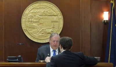 House Speaker Mike Chenault, R-Nikiski, confers with House Majority Leader Lance Pruitt, R-Anchorage, on Friday, April 25, 2014, in Juneau, Alaska. (AP Photo/Becky Bohrer)