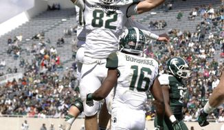 White team's Josiah Price (82) celebrates his game-winning touchdown reception with quarterback Connor Cook, rear, and Aaron Burbridge (16) with seconds remaining in Michigan State's NCAA college football scrimmage, Saturday, April 26, 2014, in East Lansing, Mich. The White team defeated the Green team 20-13. (AP Photo/Al Goldis)