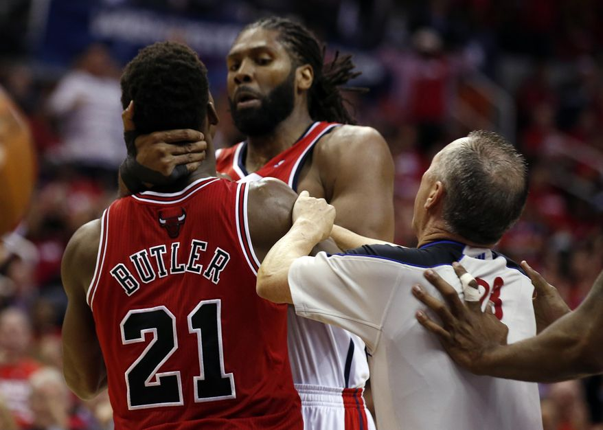 Referee Jason Phillips moves to separate Chicago Bulls guard Jimmy Butler (21) and Washington Wizards forward Nene, center, from Brazil, in the second half of Game 3 of an opening-round NBA basketball playoff series on Friday, April 25, 2014, in Washington. Nene received a double technical and was ejected. The Bulls won 100-97. (AP Photo/Alex Brandon)
