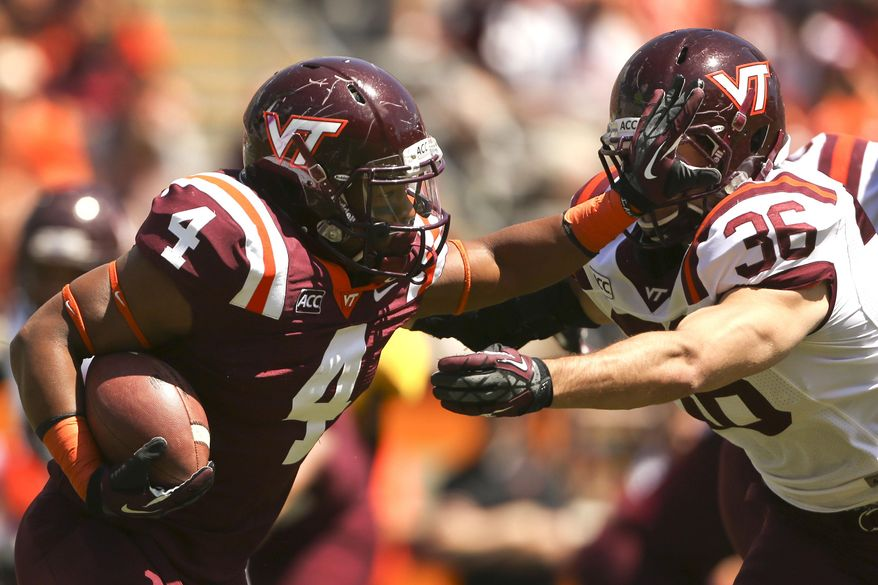 Maroon Team running back J.C. Coleman (4)  pushes off on White Team defender Chase Williams (36) during their spring NCAA college football game in Blacksburg, Va., Saturday April 26 2014. (AP Photo/The Roanoke Times, Matt Gentry) LOCAL TV OUT; SALEM TIMES REGISTER OUT; FINCASTLE HERALD OUT;  CHRISTIANBURG NEWS MESSENGER OUT; RADFORD NEWS JOURNAL OUT; ROANOKE STAR SENTINEL OUT