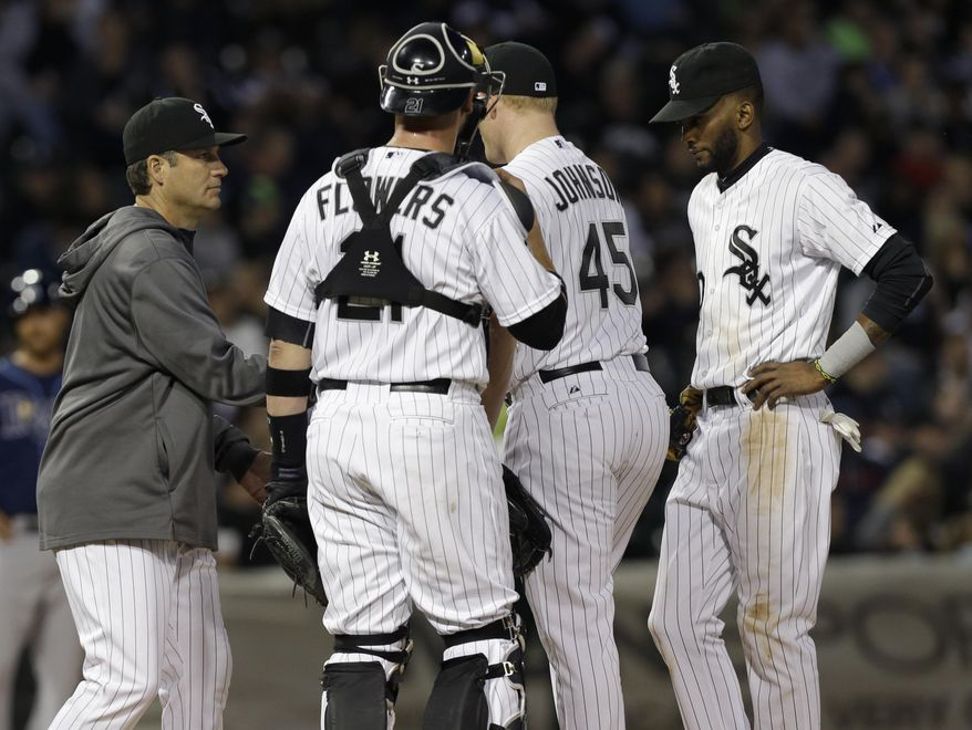 Chicago White Sox starter Erik Johnson (45) is pulled by manager Robin Ventura, left, as catcher Tyler Flowers (21) and shortstop Alexei Ramirez, right, look on during the second inning of a baseball game against the Tampa Bay Rays in Chicago on Friday, April 25, 2014. (AP Photo/Nam Y. Huh)