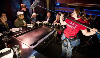 "ADVANCE FOR SUNDAY APRIL 27 AND THEREAFTER - Liberty University student Hannah Riggins operates a boom micrphone as Caleb Nelson acts as a camera assistant during the filming of ""Altar Egos"" with Liberty's Cinematic Arts program, Friday, April 18, 2014 at Wasabi Japanese Steakhouse and Sushi Bar in Lynchburg, Va.  (AP Photo/The News & Advance, Jill Nance)"