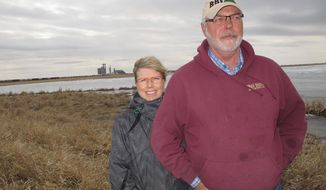 ADVANCE FOR SUNDAY, APRIL 27 AND THEREAFTER.  - Curt and Lesley Trulson, of rural Ross, stand at the slough on their land, which has swallowed up 350 crop acres since 2008. The Trulsons, like others in Mountrail County, plan to sell up to 300 acre feet to Oasis Petroleum for use in hydraulic fracturing. (AP Photo/Bismarck Tribune, Lauren Donovan)