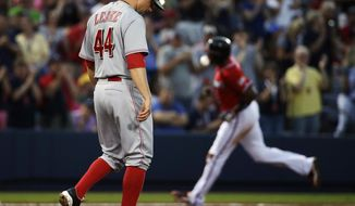 Cincinnati Reds starting pitcher Mike Leake, left, stands on the mound after giving up a home run to Atlanta Braves' Justin Upton, right, in the third inning of a baseball game, Saturday, April 26, 2014, in Atlanta. (AP Photo/David Goldman)