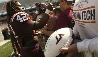 Maroon team running back Marshawn Williams (42) signs autographs for fans after Virginia Tech's annual Maroon-White spring NCAA college football game in Blacksburg, Va., Saturday, April 26 2014. (AP Photo/The Roanoke Times, Matt Gentry)