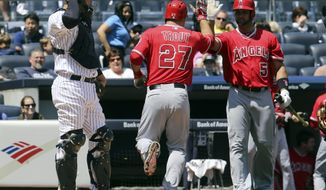 Los Angeles Angels; Mike Trout (27) high-fives teammate Albert Pujols (5) after hitting solo home run as New York Yankees catcher John Ryan Murphy stands at home plate in the first inning of a baseball game at Yankee Stadium, Saturday, April 26, 2014, in New York. (AP Photo/John Minchillo)