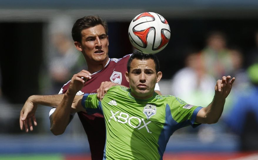 Seattle Sounders' Marco Pappa, right, and Colorado Rapids' Thomas Piermayr, left, battle for a header, Saturday, April 26, 2014, in the first half of an MLS soccer match in Seattle. (AP Photo/Ted S. Warren)