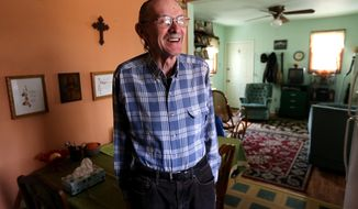 ADVANCE FOR USE SATURDAY, APRIL 26 - In this photo taken on April 16, 2014, Mike McFarland smiles in his small apartment in Dubuque, Iowa, opened it to Richard Mockmore, who was homeless, 3 years ago. The men have been close friends ever since. (AP Photo/The Telegraph Herald, Dave Kettering) MAGS OUT, TV OUT