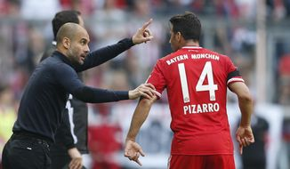Bayern head coach Pep Guardiola of Spain, left, talks to Bayern's Claudio Pizarro of Peru during the German first division Bundesliga soccer match between FC Bayern Munich and SV Werder Bremen in Munich, southern Germany, Saturday, April 26, 2014. (AP Photo/Matthias Schrader)