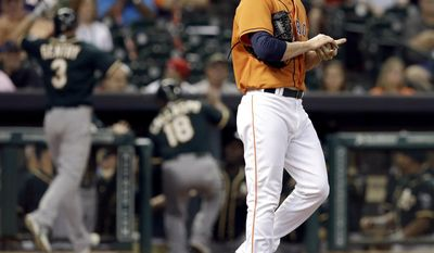 Houston Astros relief pitcher Josh Fields, right, walks back to the mound as the Oakland Athletics celebrate a three-run single with an error by Astros right fielder George Springer in the ninth inning of a baseball game Friday, April 25, 2014, in Houston. (AP Photo/Pat Sullivan)