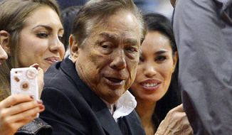 "In this photo taken on Friday, Oct. 25, 2013, Los Angeles Clippers owner Donald Sterling, center, and V. Stiviano, right, watch the Clippers play the Sacramento Kings during the first half of an NBA basketball game, in Los Angeles. The NBA is investigating a report of an audio recording in which a man purported to be Sterling makes racist remarks while speaking to Stiviano.  NBA spokesman Mike Bass said in a statement Saturday, April 26, 2014, that the league is in the process of authenticating the validity of the recording posted on TMZ's website. Bass called the comments ""disturbing and offensive.""  (AP Photo/Mark J. Terrill)"