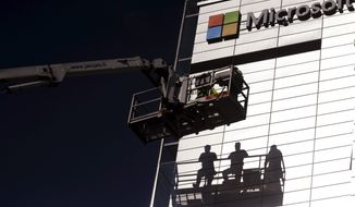 Workers install the logo of U.S. technology giant, Microsoft on the wall of Nokia's former headquarters in Espoo, Finland, Saturday, April 26, 2014. (AP Photo/Lehtikuva, Mikko Stig)