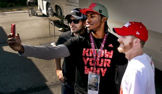 Washington Redskins quarterback Robert Griffin III, center, shoots a selfie with Jimmie Johnson, left, and Dale Earnhardt Jr. at Richmond International Raceway, Saturday, April 26, 2014. Griffin visited with the Rick Hendrick drivers before the NASCAR Sprint Cup race where is scheduled to drive the pace car at the start of Saturday's race. (AP Photo/Richmond Times-Dispatch, Skip Rowland)